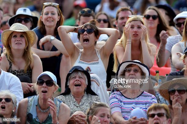 Spectators reacts as they watch a giant screen showing the men's semifinal match between Switzerland's Roger Federer and Britain's Andy Murray from...