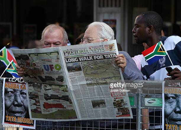 Spectators read the newspaper while waiting to see the funeral cortege of former South African president Nelson Mandela as it makes its way towards...