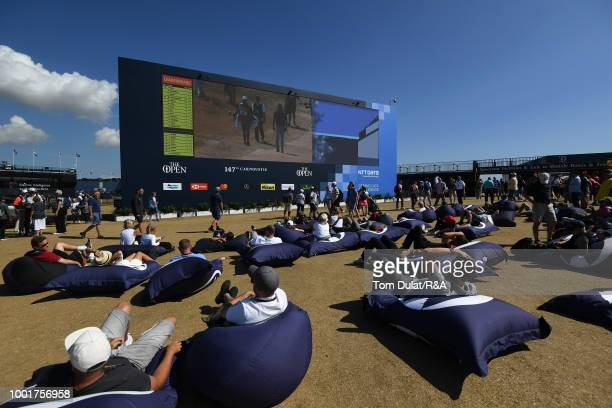 Spectators relax and watch the action on a big screen during round one of the 147th Open Championship at Carnoustie Golf Club on July 19 2018 in...