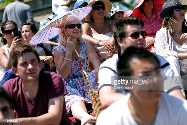 Spectators relax in the sun on Murray Mound as they watch the Gentlemen's Singles semifinal match between Novak Djokovic of Serbia and Grigor...