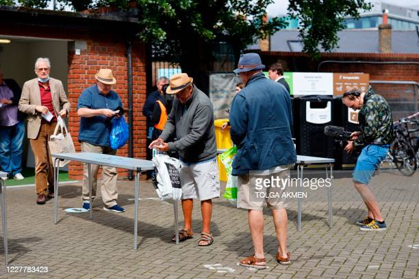 Spectators sanitise their hands as a precaution against the spread of the novel coronavirus as they arrive to watch the friendly county cricket match...
