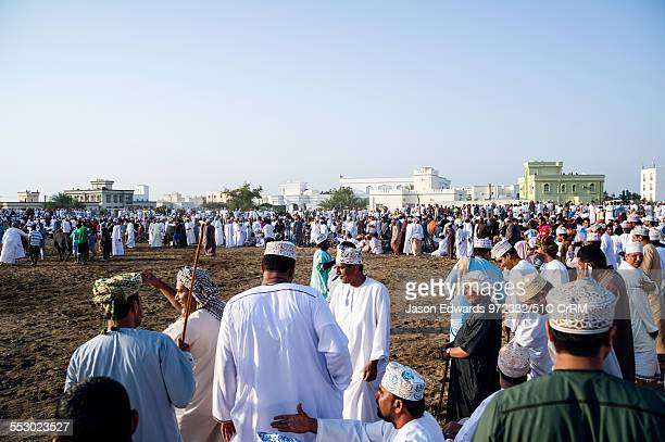 Spectators scatter on a bull ring after a Brahman bull stampeded through the crowd. Al Sharadi, Seeb, Muscat, Sultanate of Oman.