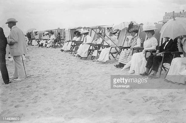 Spectators seated in beach chairs with awnings and umbrellas watch the motor boat races on a beach at Palm Beach Florida early twentieth century