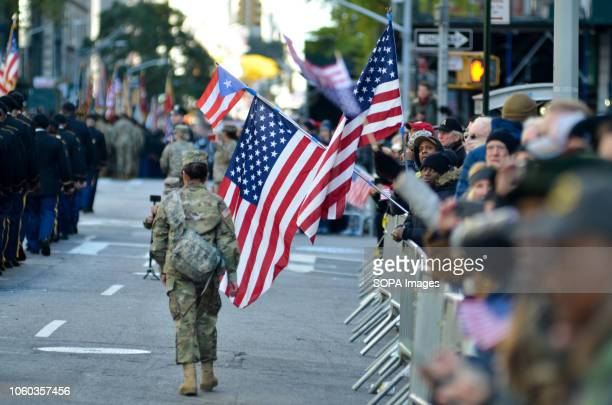 Spectators seen with American flags on the side of the street during the parade Thousands from more than 300 units in the Armed Forces took part in...