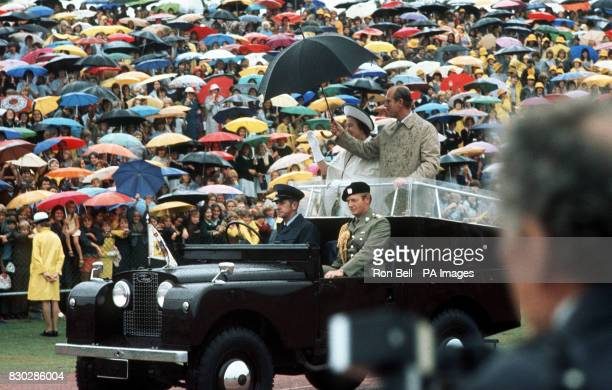 Spectators shelter beneath umbrellas and Queen Eliabeth II and the Duke of Edinburgh do likewise as they drive in a landrover when attending a school...