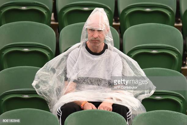 Spectators shelter during a rain delay at The All England Lawn Tennis Club in Wimbledon southwest London on July 3 2017 on the first day of the 2017...