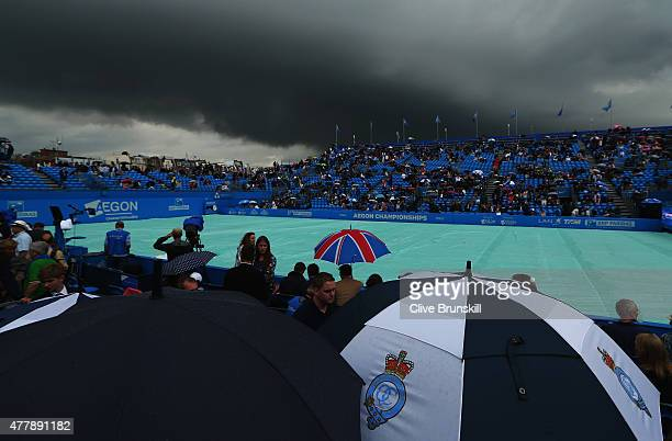 Spectators shelter from the rain as a dark rain cloud makes its way over centre court during the men's singles semi-final match between Andy Murray...