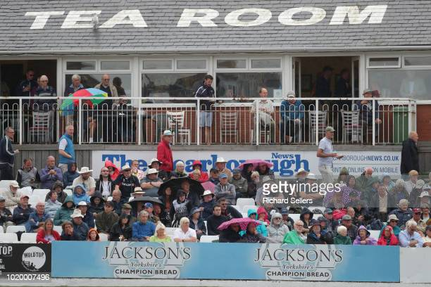 Spectators shelter from the rain under their umbrellas during day two of the Specsavers Championship Division One match between Yorkshire and...