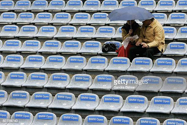 Spectators shelter under their umbrella as rain falls at the BMW Open tournament on April 27 2005 in Munich Germany