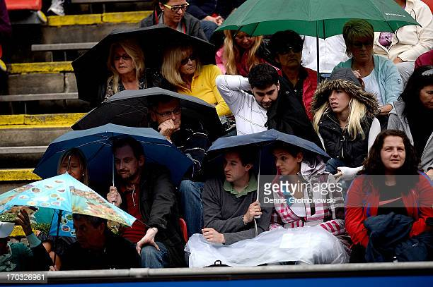 Spectators shelter under umbrellas as rain causes delays during day four of the Nuernberger Insurance Cup on June 11 2013 in Nuremberg Germany