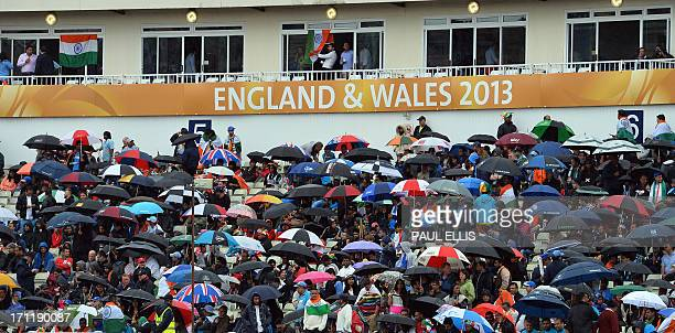 Spectators shelter under umbrellas as rain interupts the start of play in the 2013 ICC Champions Trophy Final cricket match between England and India...