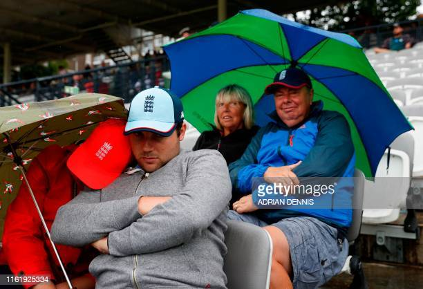Spectators shelter under umbrellas during a rain delay on the third day of the second Ashes cricket Test match between England and Australia at...