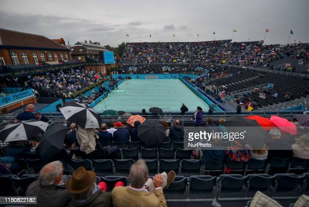 Spectators shelter under umbrellas during day three of ATP FeverTree Championships tennis tournament at Queen's Club in west London on June 19 2019