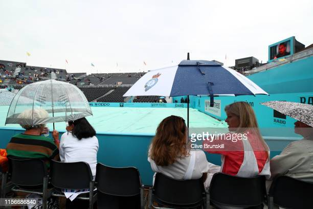Spectators shelter under umbrellas on centre court due to a rain delay during day Two of the FeverTree Championships at Queens Club on June 18 2019...
