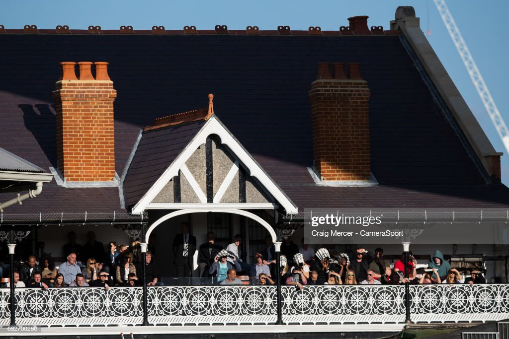 Spectators shield their eyes from the sun on the terrace of the Cottage whilst watching play during the Sky Bet Championship match between Fulham and Reading at Craven Cottage on May 13, 2017 in London, England.