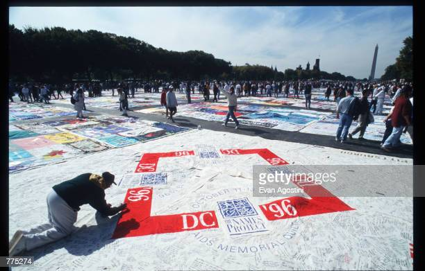 Spectators sign a panel of the National AIDS Memorial Quilt on the Mall October 12 1996 in Washington DC The AIDS Memorial Quilt is a tool for...