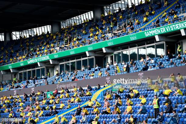 Spectators sit in the stands during the Danish Superliga football match at Broendby Stadium between Broendby IF and FC Copenhagen, on June 21, 2020....