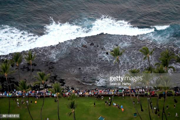 Spectators sit on a rock wall during the IRONMAN World Championship on October 14 2017 in Kailua Kona Hawaii