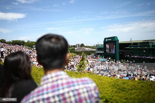 Spectators sit on Murray Mound as they watch a largescreen television showing the Centre Court Gentlemen's semifinal match between Novak Djokovic of...
