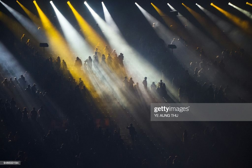 TOPSHOT - Spectators sit on the stands during a light show of the closing ceremony of the 2018 Gold Coast Commonwealth Games at the Carrara Stadium on the Gold Coast on April 15, 2018. /