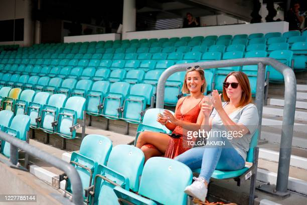 Spectators sit socially distanced leaving spaces between groups as a precaution against the spread of the novel coronavirus as they watch the...