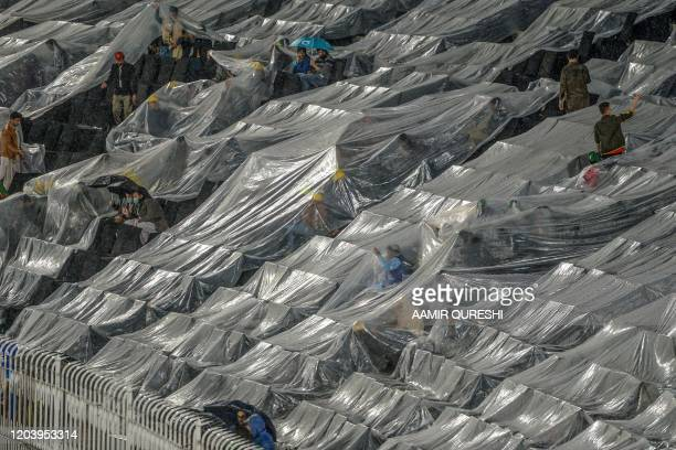 TOPSHOT Spectators sit under plastic covers during rain showers before the start of the Pakistan Super League T20 cricket match between Peshawar...