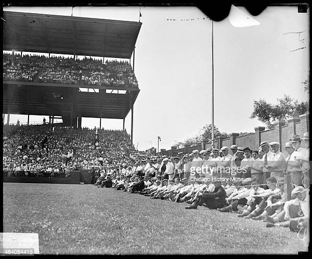 Spectators sitting and standing behind a rope barrier along the left field wall at Wrigley Field during a World Series game between the National...