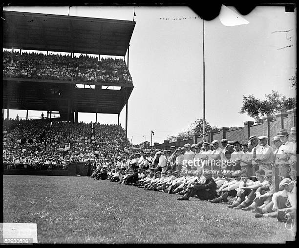 Spectators sitting and standing behind a rope barrier along the left field wall at Wrigley Field in Chicago Illinois during a 1929 World Series game...