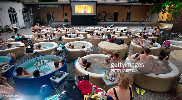 Spectators sitting in whirlpools together watch the film 'Pulp Fiction' shown on a large screen on Prater Island in Munich on July 3 2015 AFP PHOTO /...