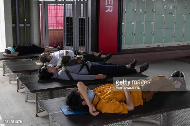 Spectators sleep on benches during the men's cycling road individual time trial during the Tokyo 2020 Olympic Games at the Fuji International...