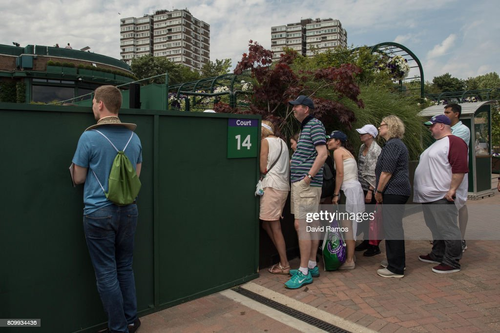 Spectators sneak a look through the fence in the outside courts on day four of the Wimbledon Lawn Tennis Championships at the All England Lawn Tennis and Croquet Club on July 6, 2017 in London, England.