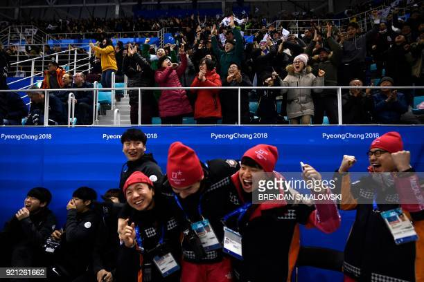 Spectators staff and emergency personnel react to a goal by South Korea in the men's playoffs qualifications ice hockey match between Finland and...