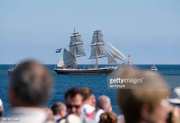 Spectators stand and watch as the North Sea Tall Ships Parade of Sail leaves Blyth harbour on August 29 2016 in Blyth England The bustling port town...