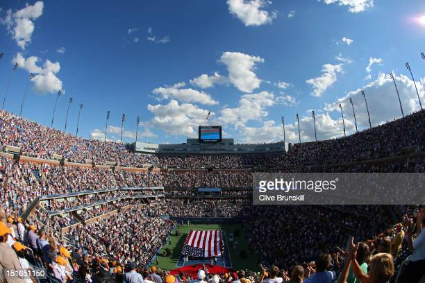 Spectators stand as members of the military unfurl the national flag inside Arthur Ashe Stadium before the start of the women's singles final match...