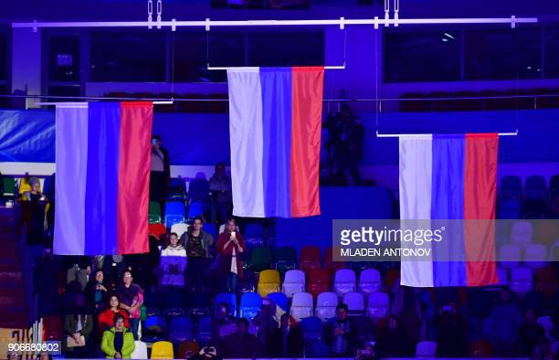 Spectators stand as they listen to the national anthem during the flagraising ceremony for gold medallists Evgenia Tarasova and Vladimir Morozov of...
