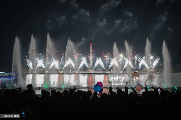 Spectators stand before a fireworks display over the Taedong river during celebrations marking the anniversary of the birth of late North Korean...