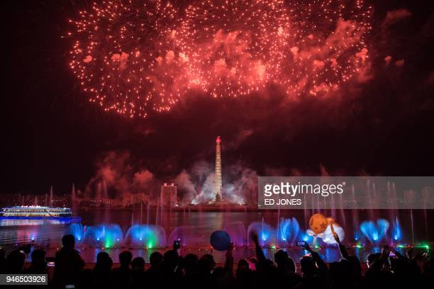 TOPSHOT Spectators stand before a fireworks display over the Taedong river during celebrations marking the anniversary of the birth of late North...