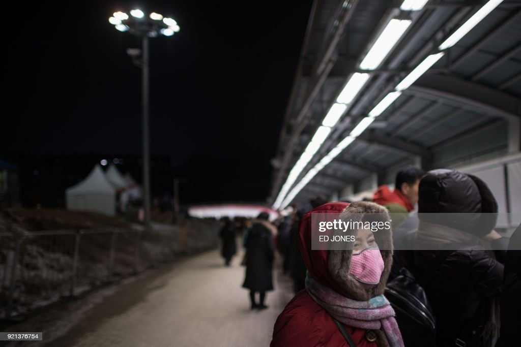 Spectators stand beside the track during the women's bobsleigh heats during the Pyeongchang 2018 Winter Olympic Games at the Olympic Sliding Centre in Pyeongchang on February 20, 2018. / AFP PHOTO / Ed JONES