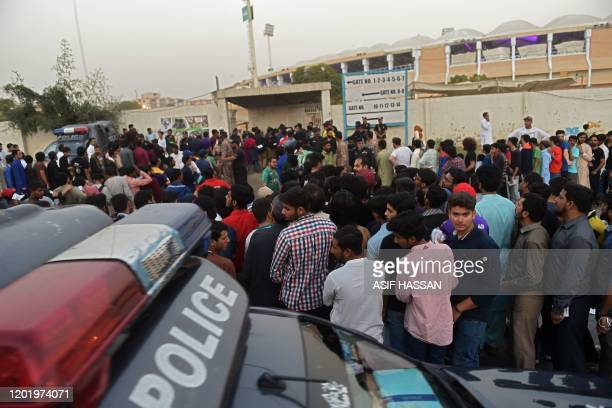 Spectators stand in a queue to enter the National Cricket Stadium in Karachi on February 20 ahead of the start of the Pakistan Super League T20...
