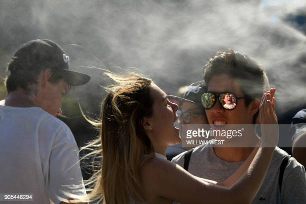 Spectators stand in front of a mist machine to cool off during warm weather on day two of the Australian Open tennis tournament in Melbourne on...