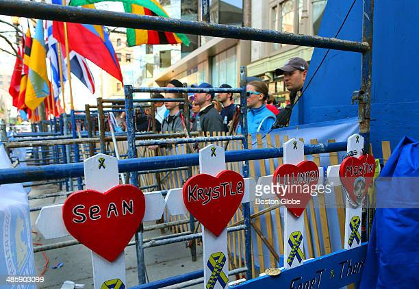 Spectators stand near a small memorial of crosses bearing the names of the victims of the 2013 Boston Marathon tucked away next to the sidewalk on...