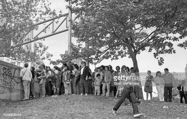 Spectators stand on a hill during the Brooklyn Bridge's 100th birthday celebrations in Brooklyn New York New York May 24 1983