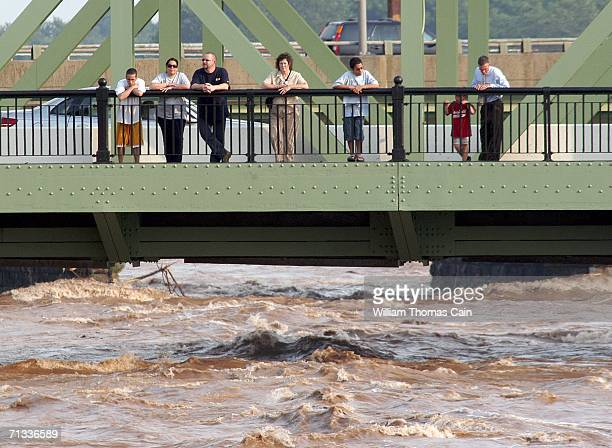 Spectators stand on bridge over the Delaware River and watch the flood waters rush past on June 29 2006 in Trenton New Jersey Gov Jon S Corzine of...