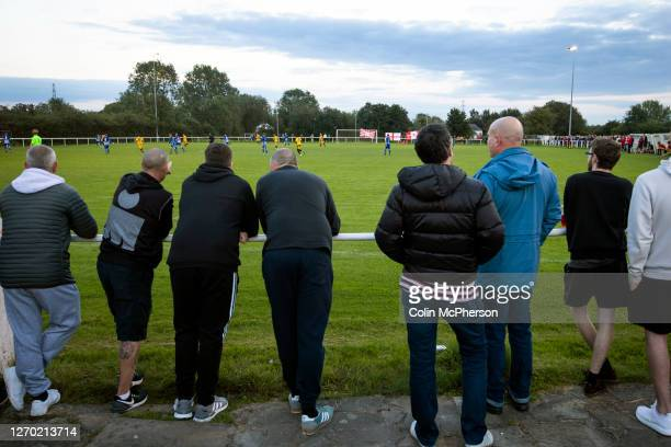Spectators standing at the perimeter fence watching the firsthalf action during the FA Cup Extra Preliminary Round between Daisy Hill and Colne at...