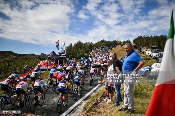Spectators standing by the Italian flag watch riders compete in the Women's Elite Road Race, a 143-kilometer route around Imola, Emilia-Romagna,...