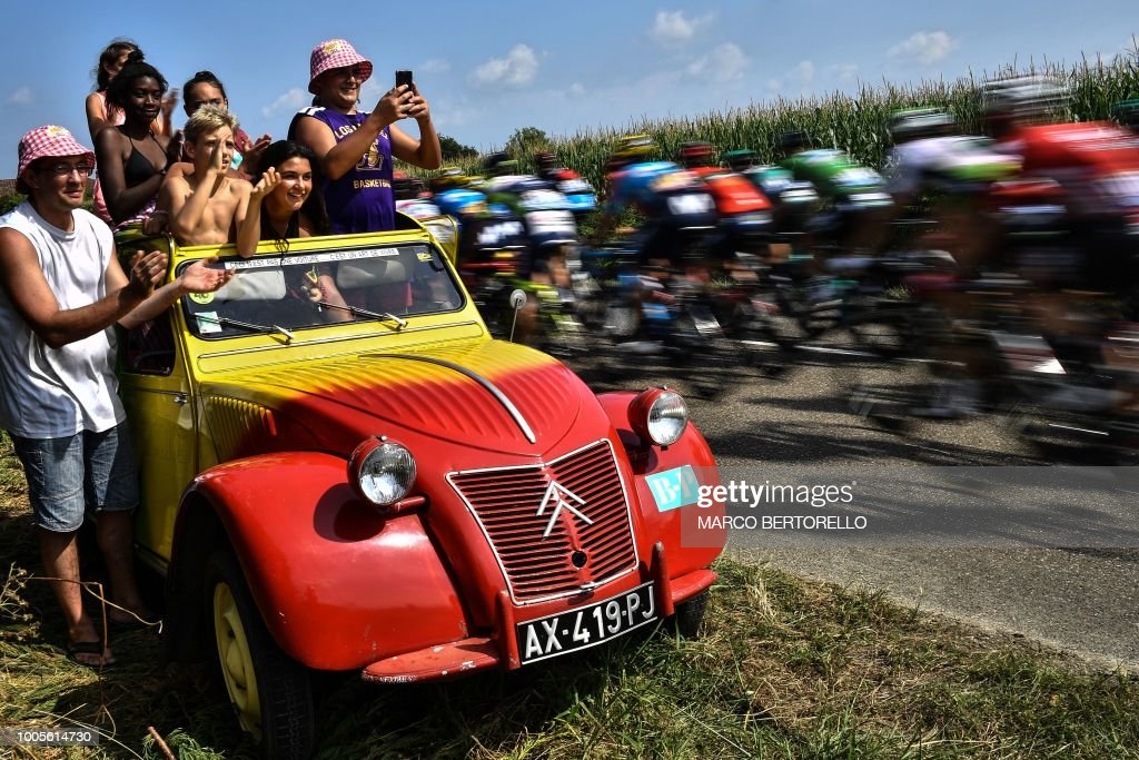 TOPSHOT - Spectators standing in a 2CV Citroen cheer as the pack rides past during the 18th stage of the 105th edition of the Tour de France cycling race, on July 26, 2018 between Trie-sur-Baise and Pau, southwestern France.