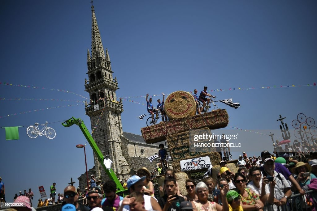 TOPSHOT - Spectators standing on haystacks wait to watch riders by the church of Plouneventer during the sixth stage of the 105th edition of the Tour de France cycling race between Brest and Mur-de-Bretagne Guerledan, western France, on July 12, 2018.