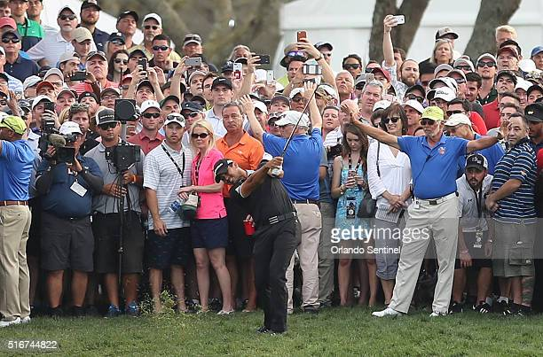 Spectators surround Jason Day as he hits his approach shot to the 18th green during the Arnold Palmer Invitational at Bay Hill Club Lodge in Orlando...