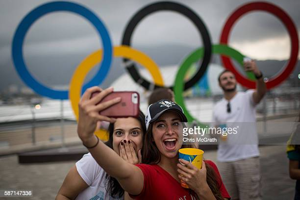 Spectators take a selfie in front of the Olympic rings at Olympic Park on Day 2 of the Rio 2016 Olympic Games on August 7 2016 in Rio de Janeiro...