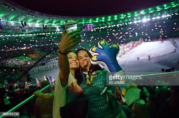 TOPSHOT Spectators take a 'selfie' picture during the closing ceremony of the Rio 2016 Olympic Games at the Maracana stadium in Rio de Janeiro on...